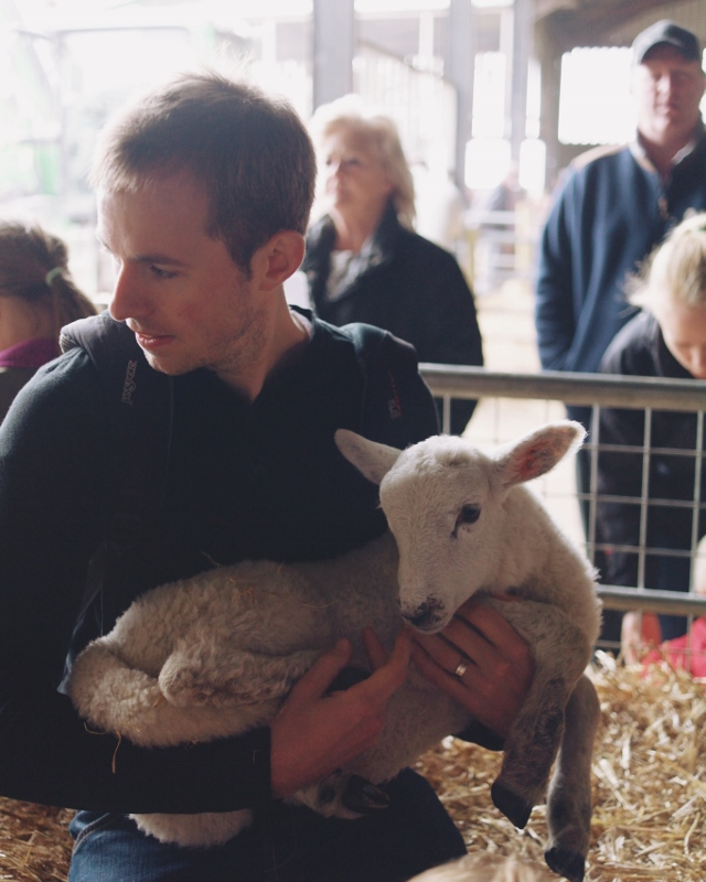 there is a man holding a lamb here, and I think my attractiveness meter just exploded